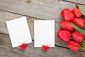 Fresh tulips and photo frames with candy hearts