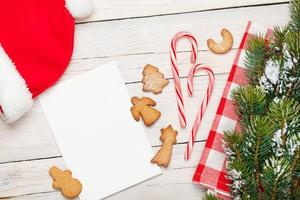 Christmas greeting card, santa hat, gingerbread cookies and snow
