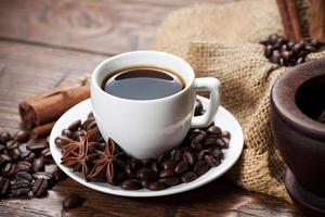 Cup of coffee with beans and spicery photo