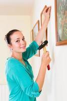 Chica colgando cuadros en marcos de pared en casa