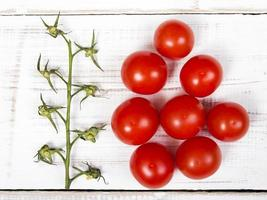 tomates cherry sobre fondo blanco de madera foto
