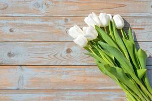 Ramo de tulipanes blancos con espacio vacío en madera vieja foto