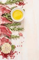 Raw  lamb chops with oil and spices on wooden background