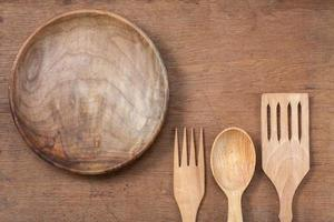 Wooden plate, fork and spoon on oak wood texture background photo