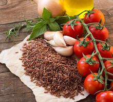 Organic red rice on  wooden background