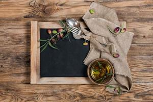 Overhead view of olive oil with olive twig and  napkin