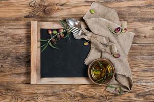Vista aérea de aceite de oliva con ramita de olivo y servilleta