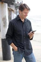 Man communicating with smart phone at beach