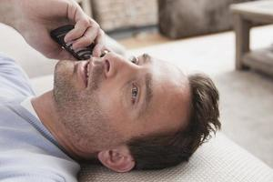 Germany, Man lying on couch using mobile phone photo