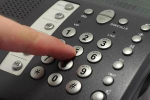 Dailing number 5 on a black telephone