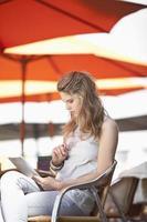 jovem sentada em um café de rua com tablet digital