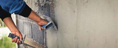 Concrete plasterer working on a house