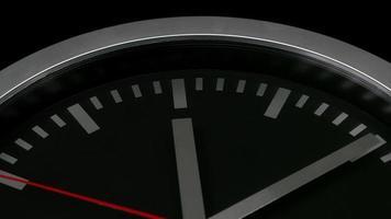 Nahaufnahme einer schwarzen Wanduhr lokalisiert auf schwarzem Hintergrund, zeigt zehn nach zwölf