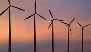 Wind turbines against red sky photo