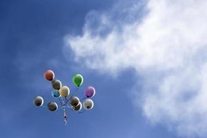 Balloons ascending into blues skies photo