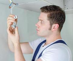 gecertificeerde elektricien die stopcontact voor gloeilamp installeert