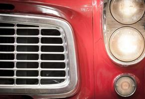 Close Up of Grille and Headlights of Red Vehicle photo