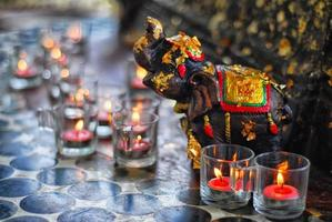 Candles with an elephant sculpture sacrifice in the temple