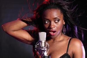 Beautiful black girl makes music singing on stage photo