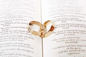 Two wedding rings on a bible, Corinthians Chapter 13