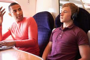 jonge man treinreizigers storen met luide muziek