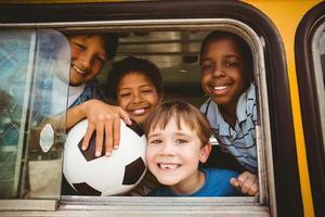 crianças olhando para fora de um ônibus escolar