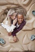 Girls on playground telling secrets