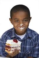 Boy eating slice of cream cake, smiling, close-up, cut out