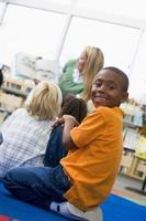 Maestra de jardín de infantes leyendo a los niños, niño mirando por encima del hombro