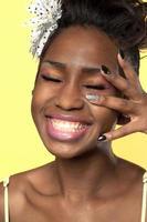 gelukkig lachend zwarte vrouw met versierde vingers op haar gezicht
