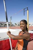 Young female pole vault athlete with pole by bar, smiling