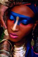 Hermosa mujer negra con maquillaje de color con ornamentación dorada