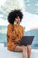 Portrait of attractive afro woman using mobile phone and laptop photo