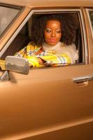 Retro 70s fashion african american woman driving in gold car.
