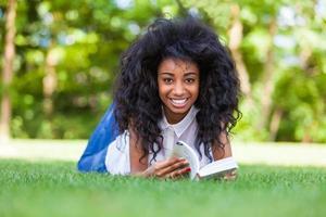 niña estudiante leyendo un libro en el parque escolar