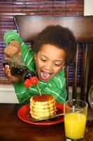 Boy pouring syrup on waffles