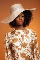 Retro 70s fashion afro woman with paisley dress and hat.