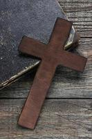 Cross and old book on wooden table