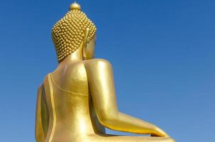 Back side of golden buddha with deep blue sky background photo