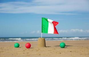 plage, mer, seaux, pelles et boule colorée avec drapeau italien