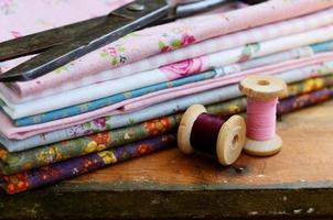 Set of different fabrics, wooden thread spools and tailor scissors