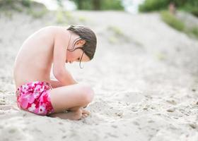 Little girl sitting on sand at the beach