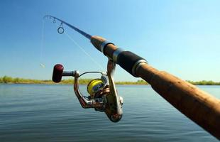 Close up of fishing rod over lake with blue sky background