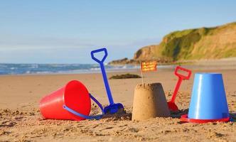 praia, mar, baldes, pás e bandeira galesa