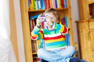Little kid boy making photos with photocamera, indoors