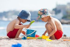 dois filhos fofos, brincando na areia na praia