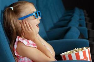 niña encantada viendo la película en el cine