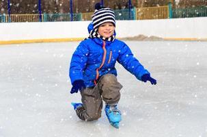 süßer kleiner Junge, der im Winter Skaten lernt