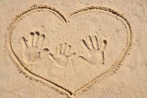 Dibujo de corazón con impresión de mano familiar en arena. foto