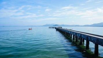 Single boat driving next to a pier Thailand photo